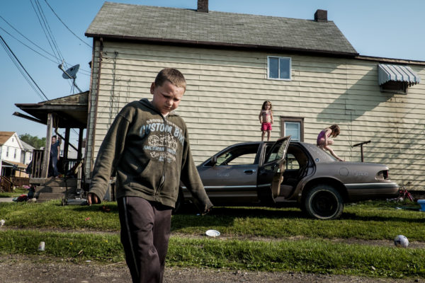 Children play on their dad's demolition derby car outside of their home in West Aliquippa, Pennsylvania, USA on May 8, 2015.  Since 1987, the city has been designated as a distressed municipality under the state's Act 47, a law that created a recovery program that's helped some 29 municipalities in the state stay afloat.  The city now has fewer residents now than the local steel mill had employees (14,000) in its heyday. The mill closed for good 20 years ago.   With few good job opportunities available, children who grow up in the area may be faced with tough economic times when they are ready to join the workforce.