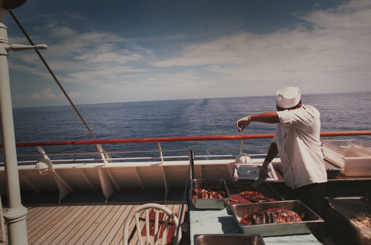A chef wipes sweat while preparing lunch on deck.