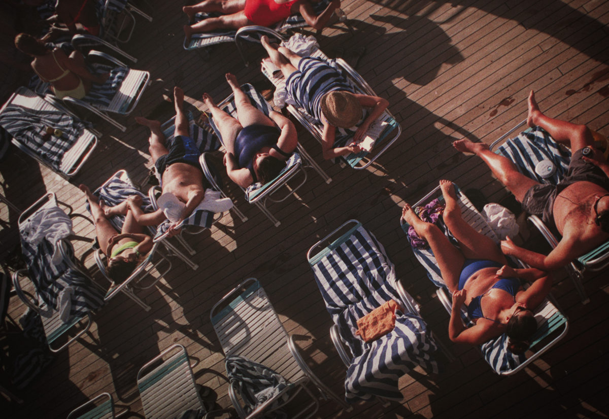 Tans and sunburn bodies are the norm atop the promenade deck of an ocean liner.